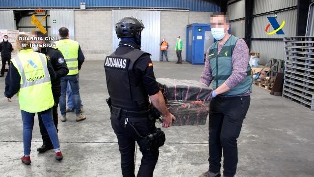 Agentes de la Guardia Civil trasladan uno de los fardos con cocaína detectados durante el pasado mes de mayo en Bilbao.