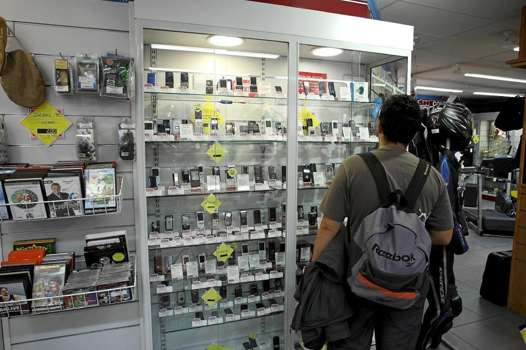Un cliente observa la oferta de telefonía móvil de la tienda de segunda man