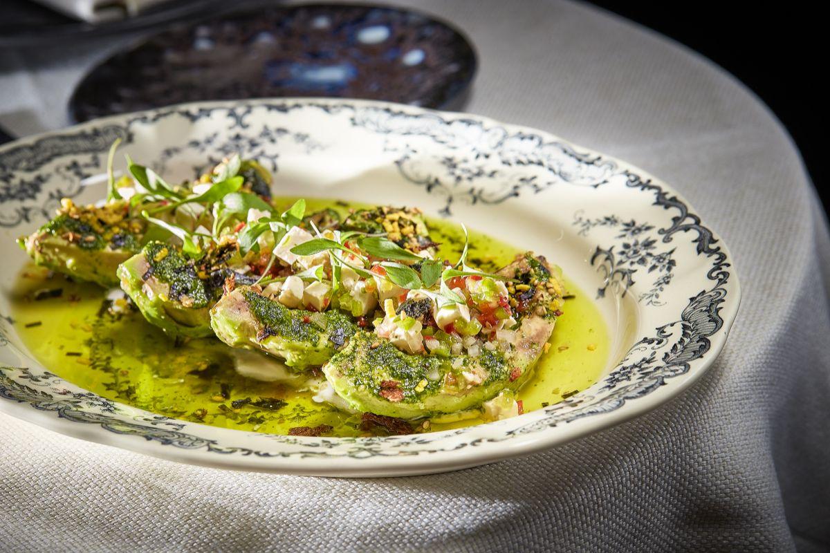 Aguacate a la brasa con pesto de cilantro joven y salpicón vegetal.