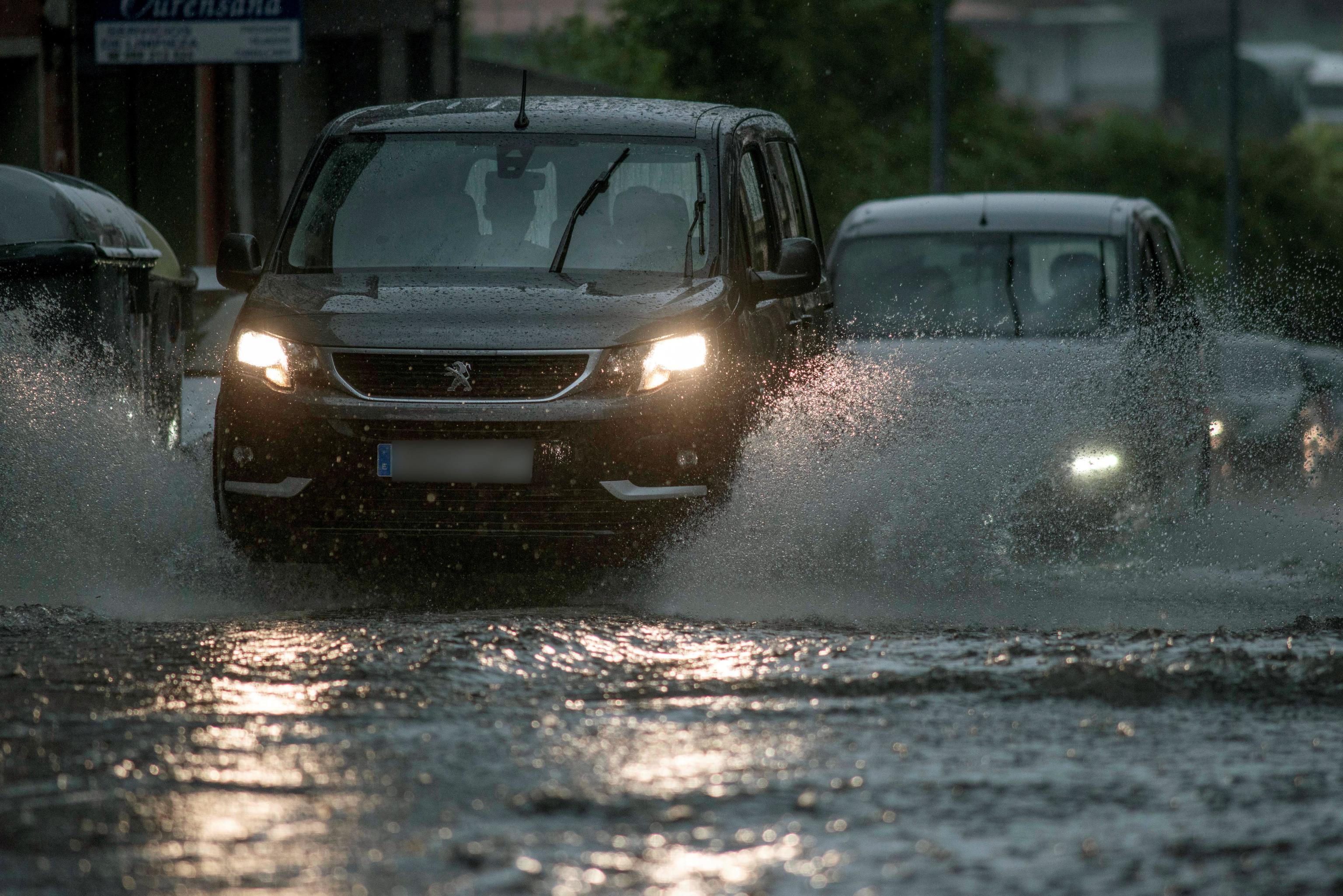 Varios vehículos circulan ayer bajo una intensa lluvia en Orense.
