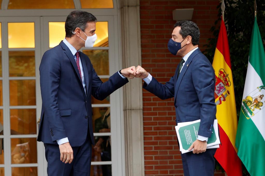 El presidente de la Junta, Juanma Moreno, saluda al presidente del Gobierno, Pedro Sánchez, este jueves a las puertas del Palacio de la Moncloa.