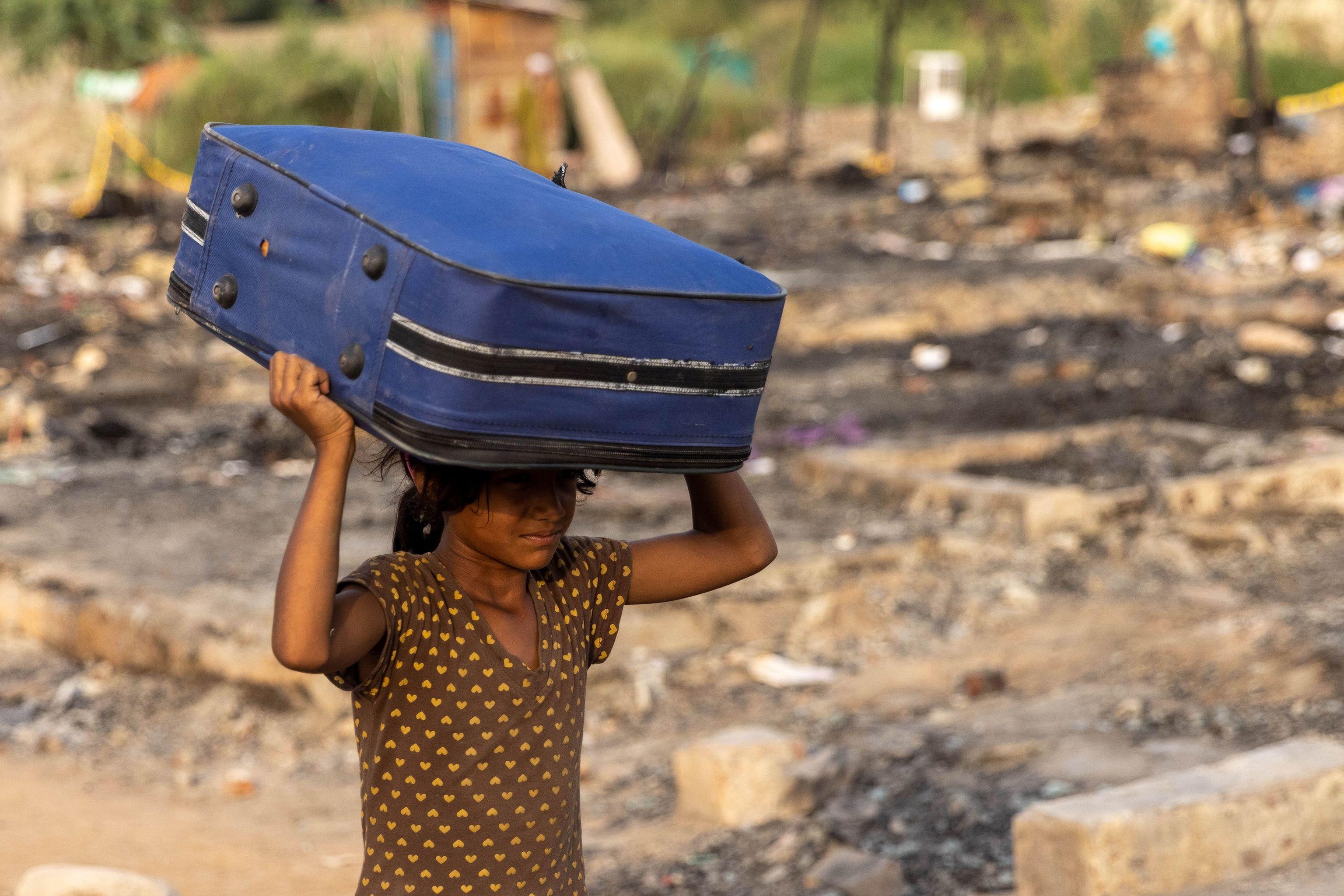 Una refugiada rohingya carga sus pertenencias en Nueva Delhi.