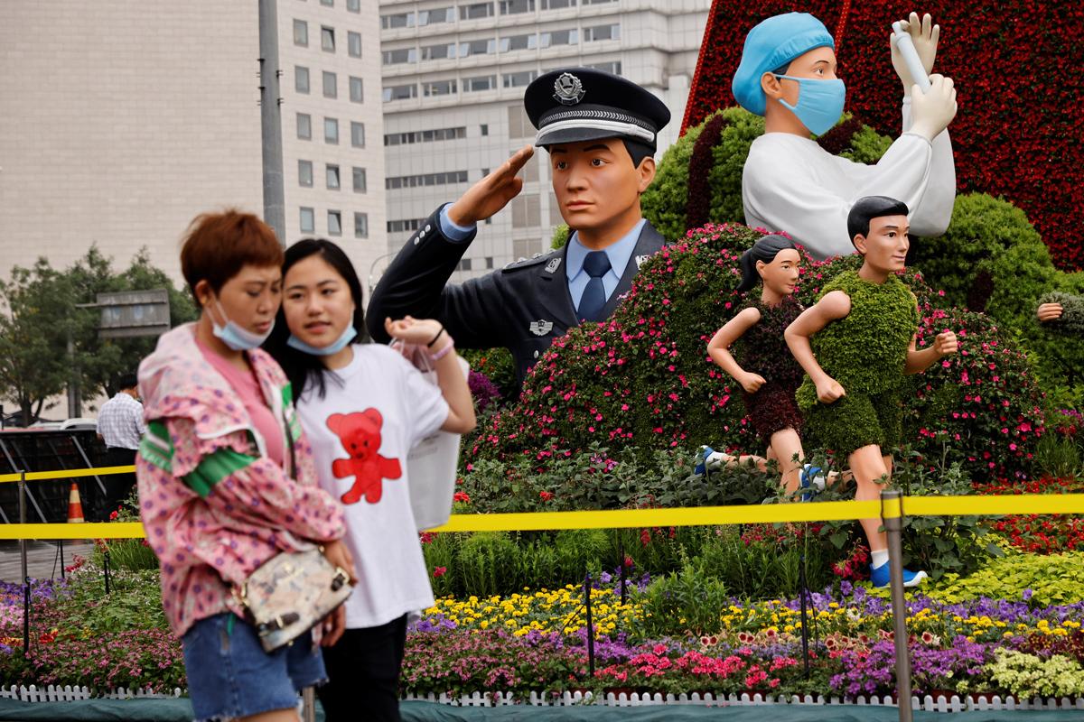 Dos jóvenes, junto a un homenaje al Partido Comunista, en Pekín.
