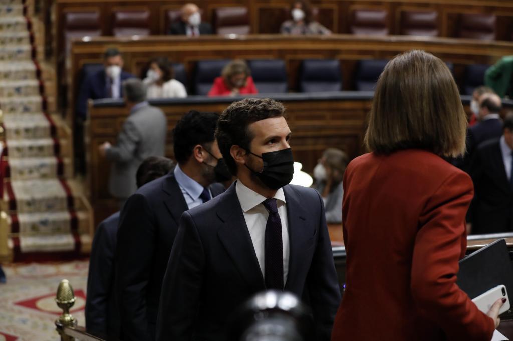 Pablo Casado se dirige a su escaño, con Pedro Sánchez al fondo, en un pleno del Congreso.
