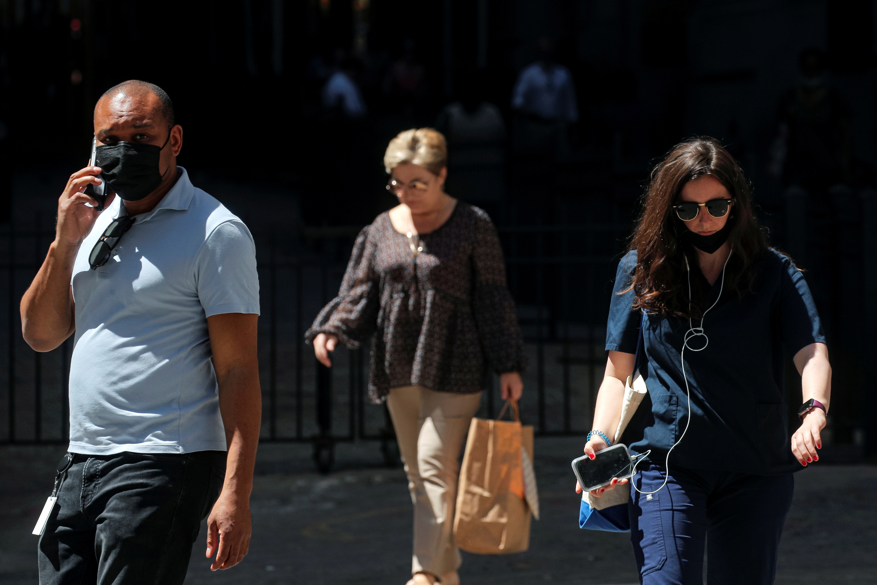 Several people walk down Wall Street (New York), after the relaxation of prevention measures against Covid.