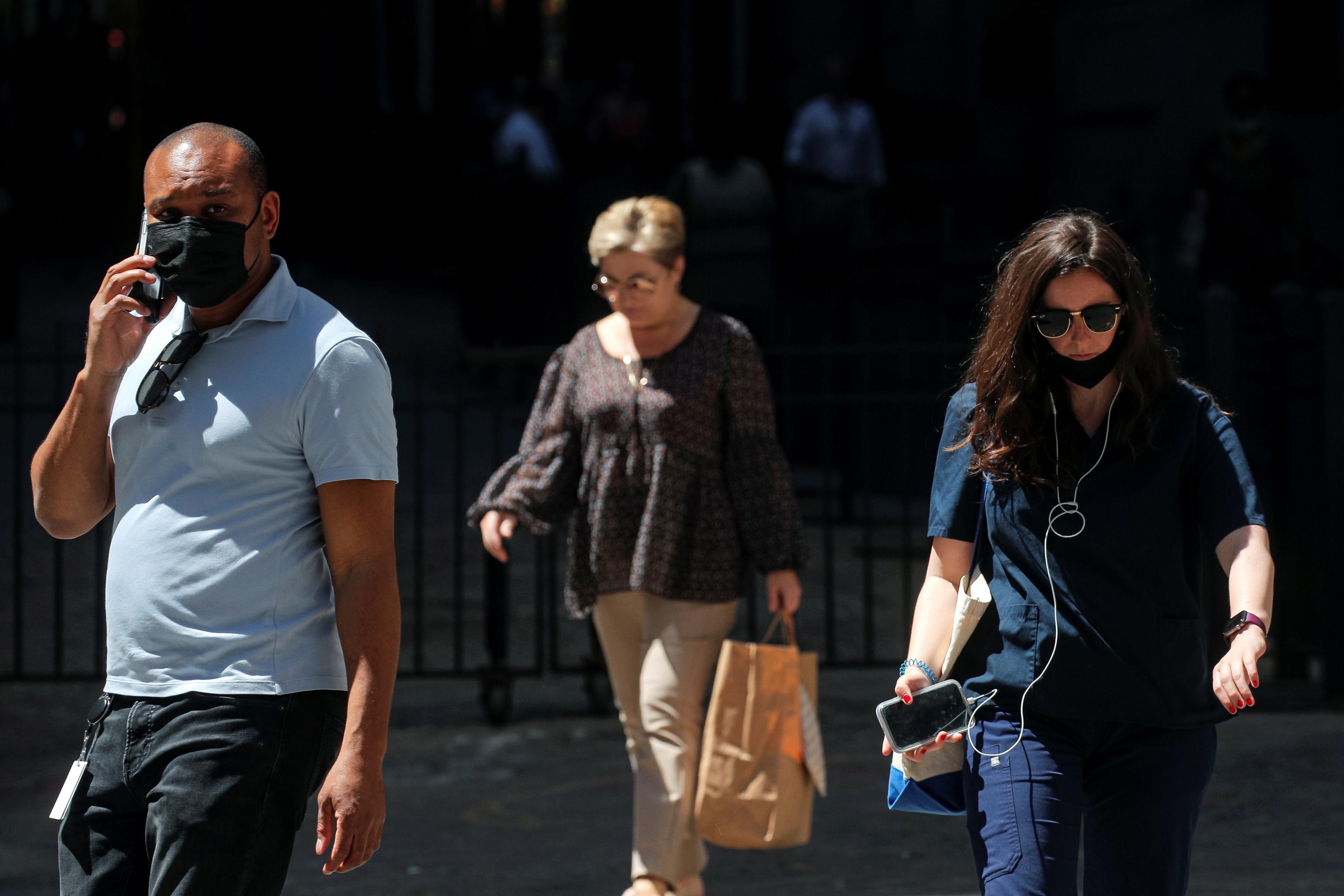 Varias personas caminan por Wall Street (Nueva York), tras la relajación de las medidas de prevención contra el Covid.