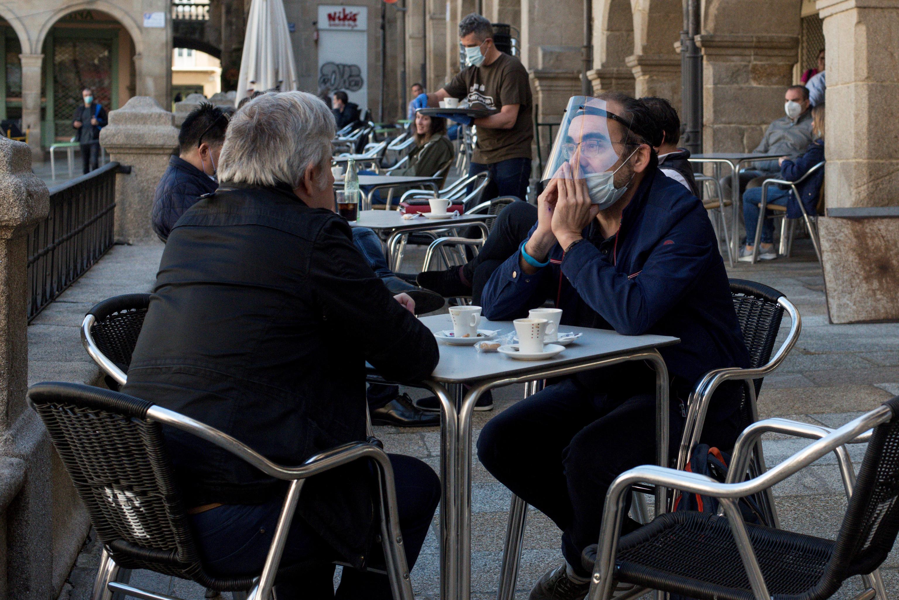 Varios ciudadanos se toman un café en la terraza de un bar en la Plaza Mayor de Orense.