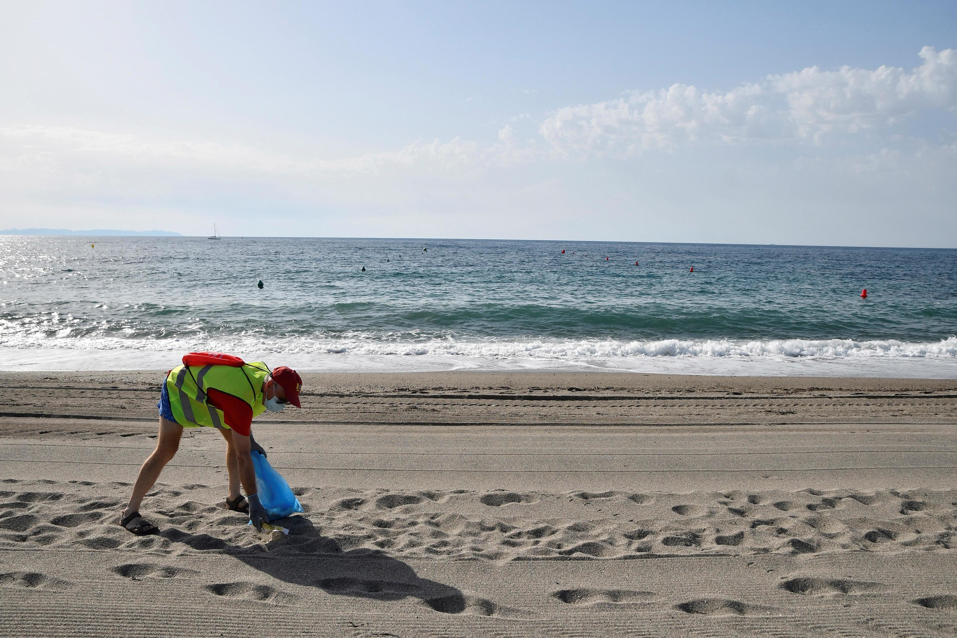 Voluntarios de Cruz Roja ayudan a recoger una playa de Almería.