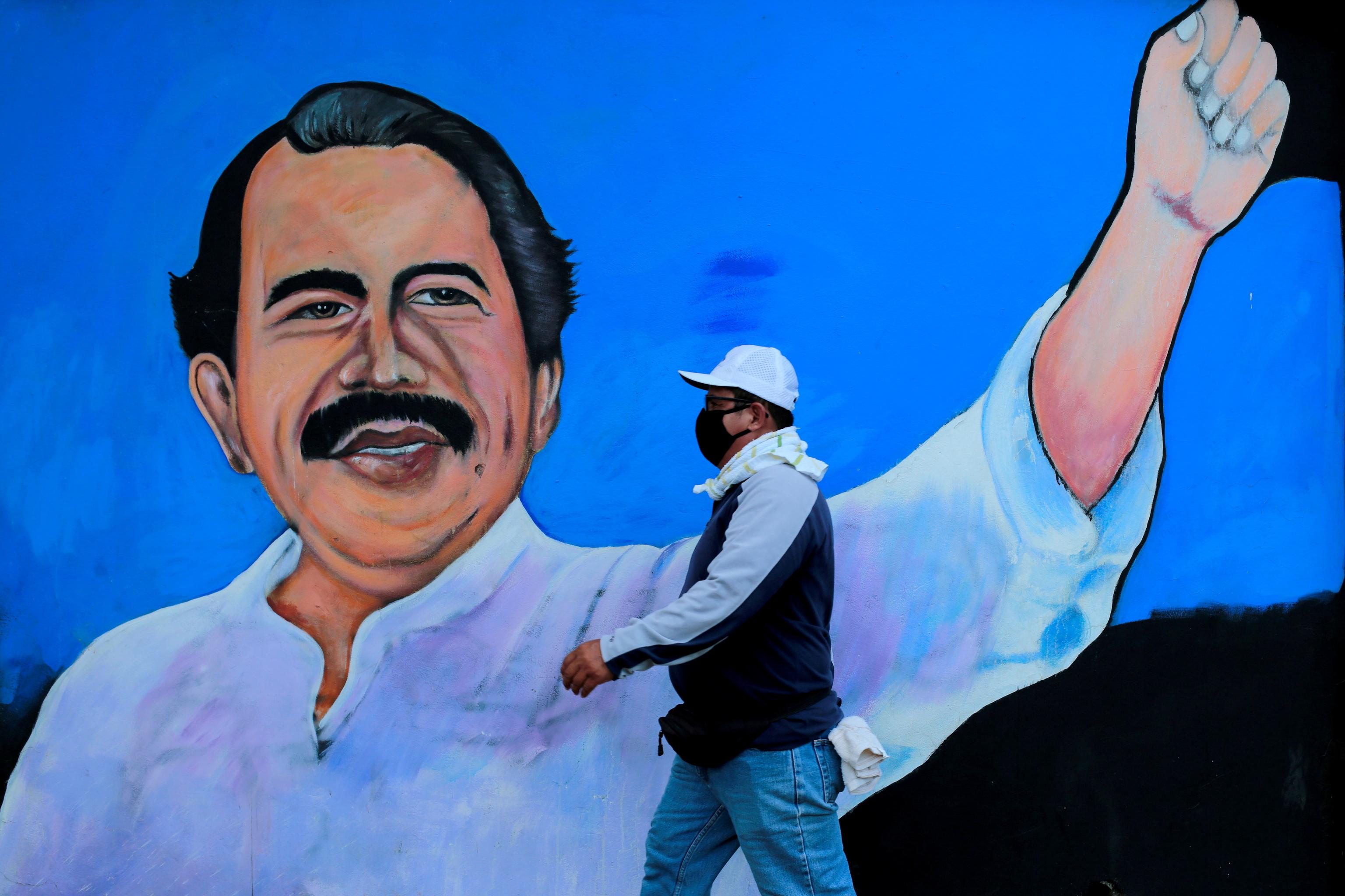 Un hombre camina delante de un mural dedicado a Daniel Ortega.