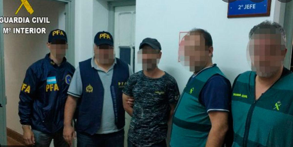 El condenado, en el centro, cuando fue detenido en Argentina.