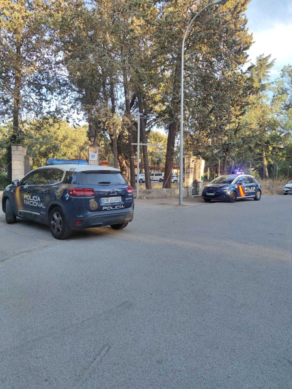 Coches de la Policía Nacional en la puerta del centro de menas de la Casa de Campo