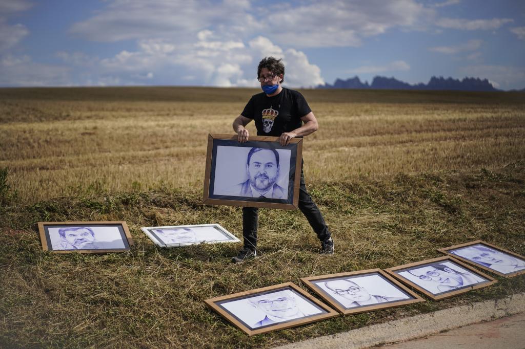 Un hombre coloca retratos de los indultados a las puertas de la cárcel de Lledoners.