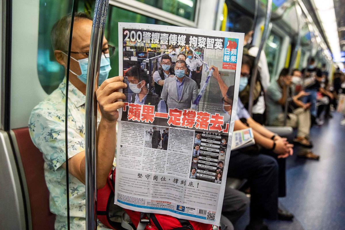 Un pasajero lee el 'Apple Daily' en un tren de Hong Kong.