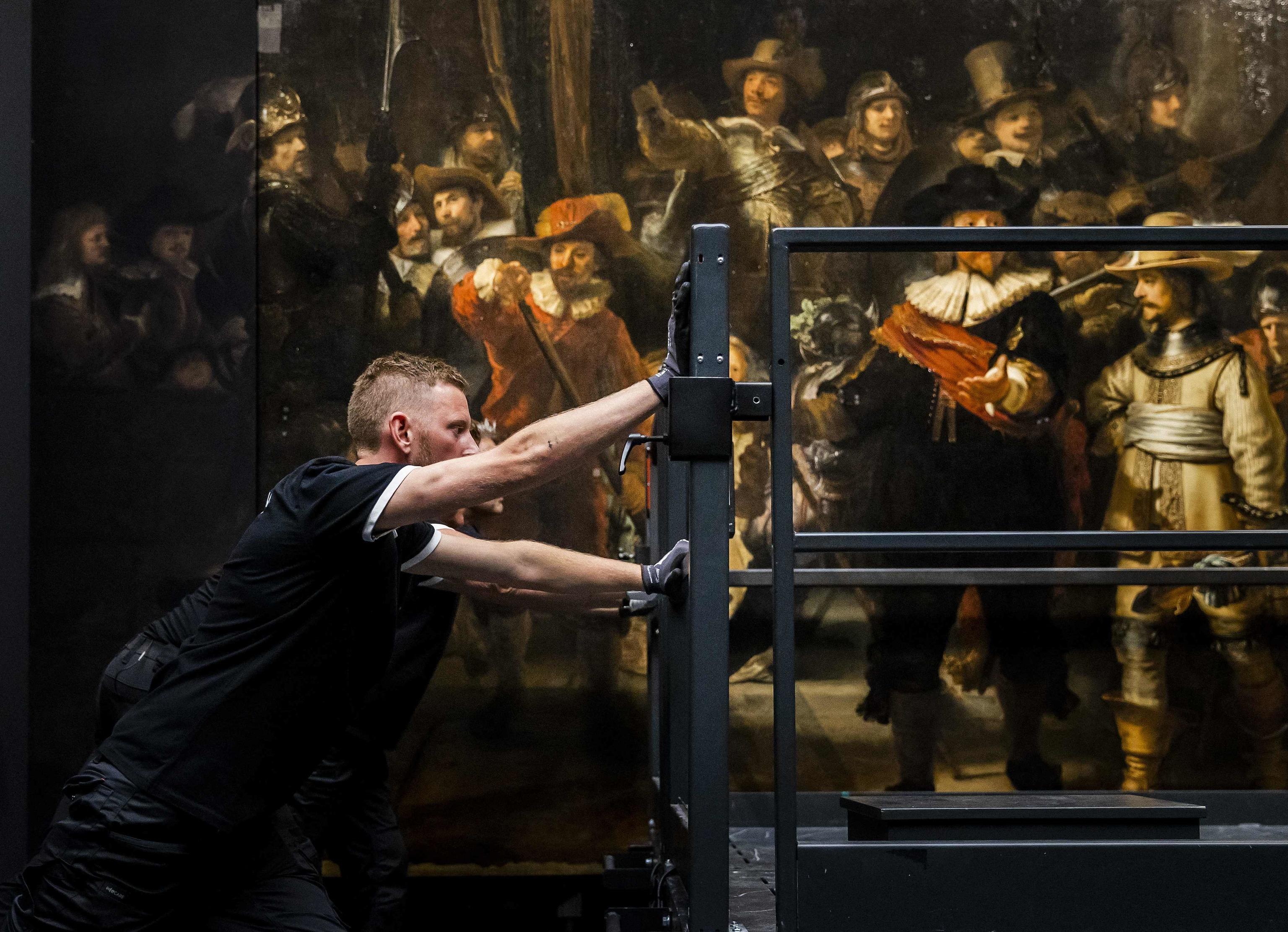 Un trabajador junto al cuadro de Rembrandt.