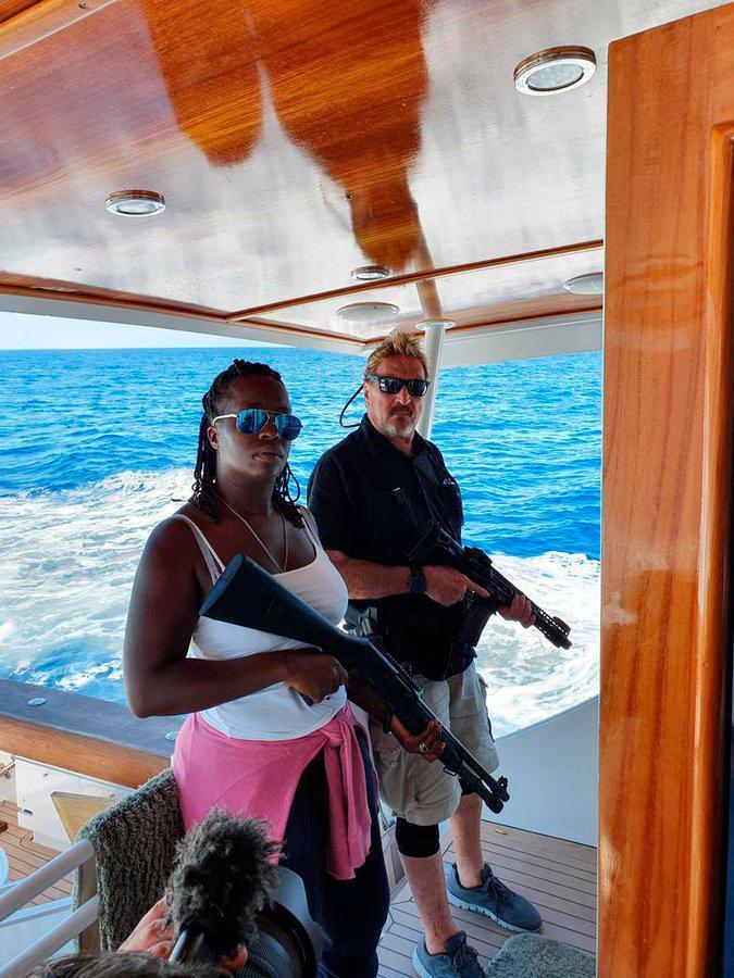 John McAfee y su última esposa posan con escopetas en su yate en el Caribe.