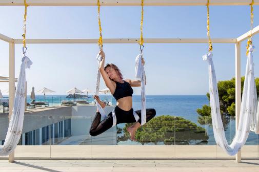 La clave de la oferta de estos hoteles son las experiencias. En la foto, una sesión de aeroyoga en la terraza del hotel ME Ibiza.