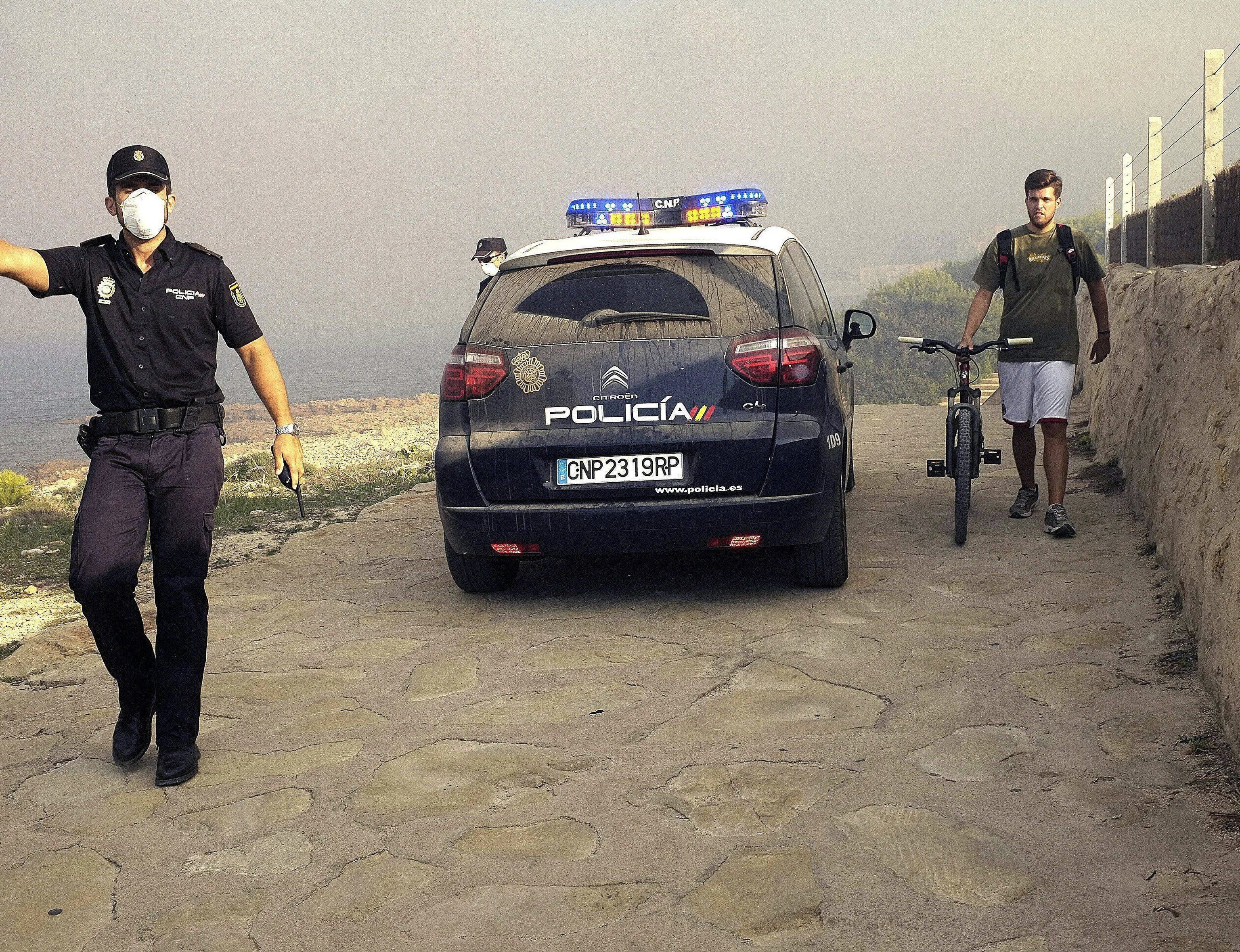 Un policia nacional procede al desalojo de los vecinos de Las Rotas (Dénia), en el incendio forestal declarado esta tarde en el término municipal de Jávea (Alicante), en Cabo de San Antonio, cerca de la zona del Montgó, en 2014.