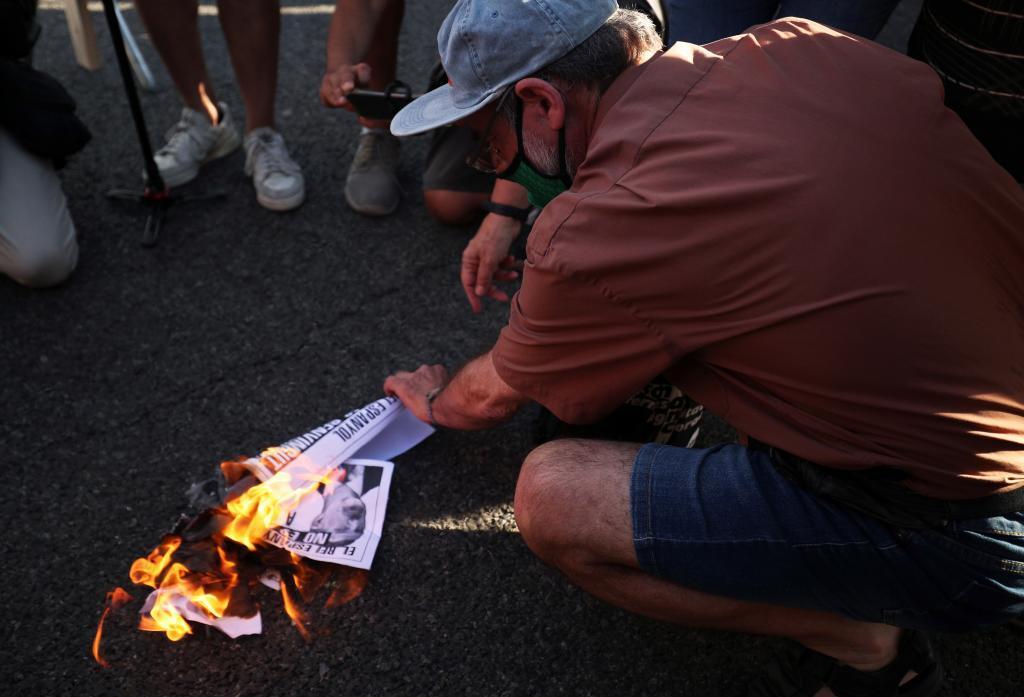 Un manifestante quema un retrato de Felipe VI en el exterior de la Fira de Barcelona.