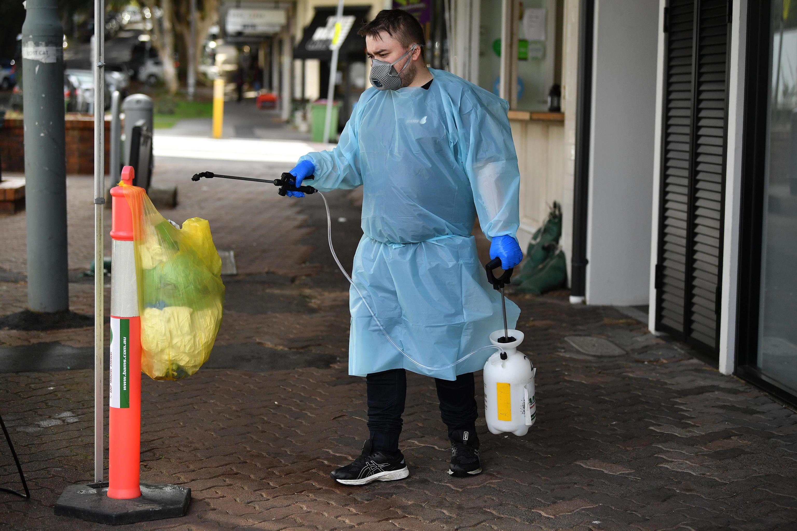 Un hombre desinfecta una papelera en Sídney.