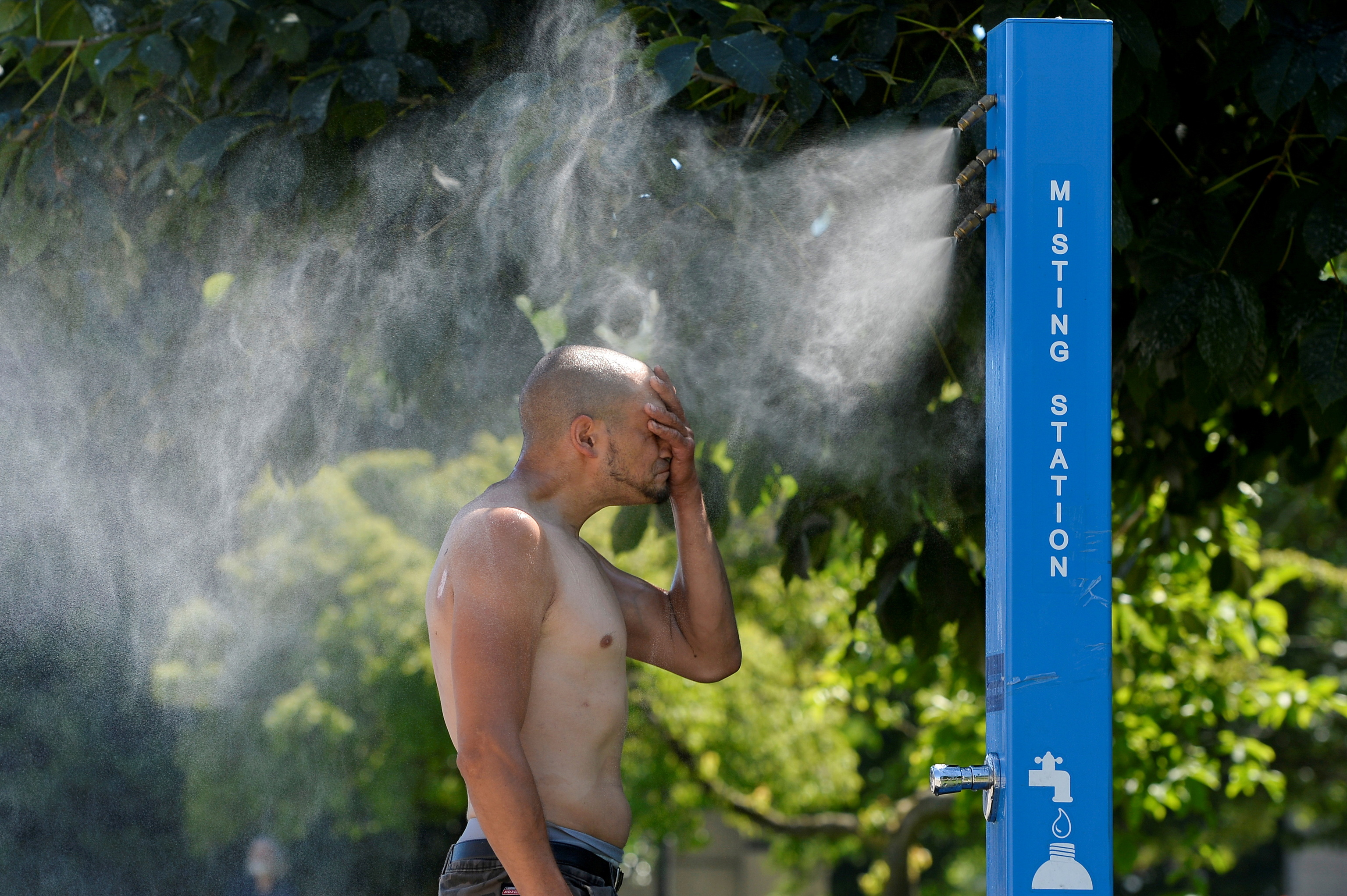 A man uses a fountain to cool off in Vancouver.