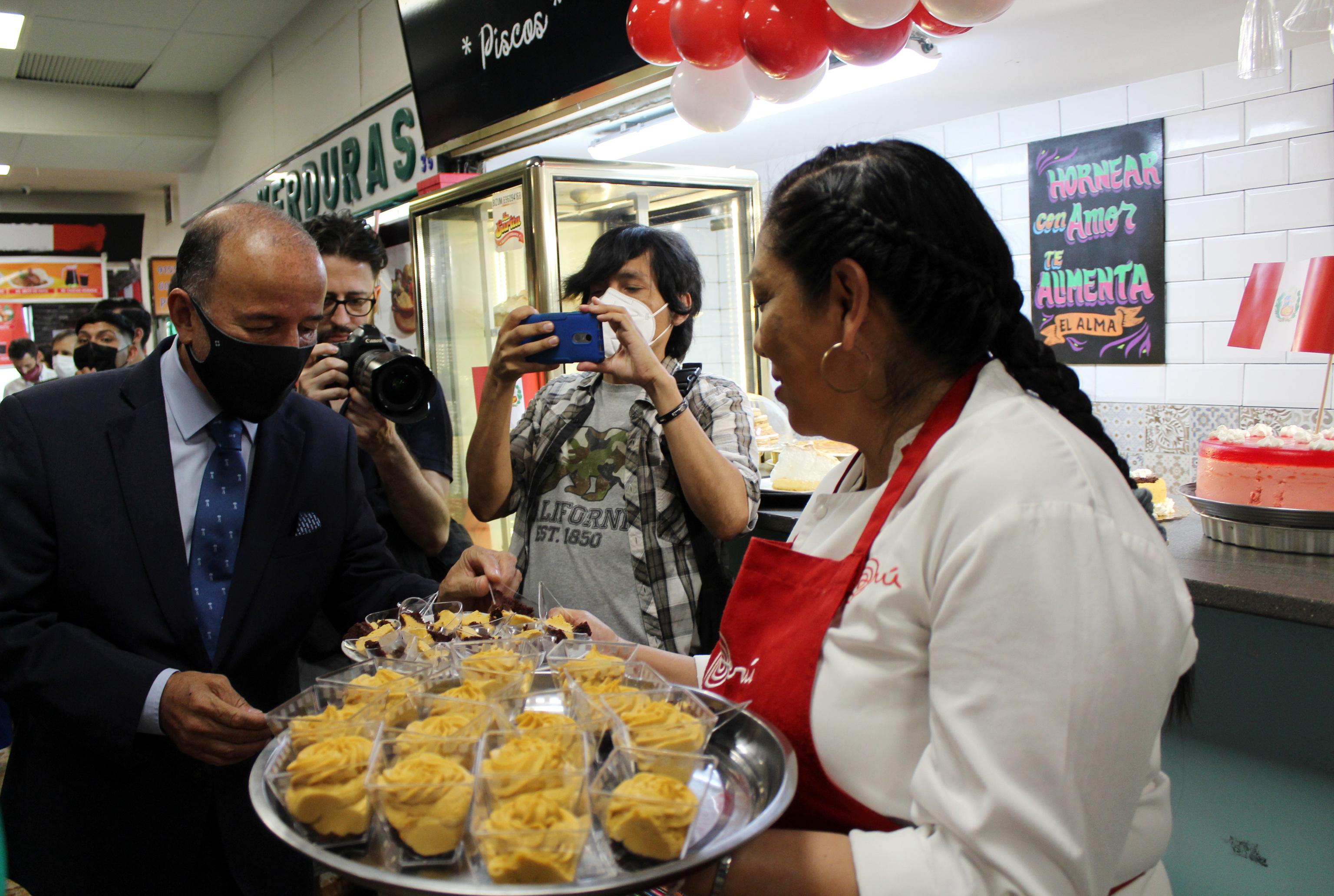 Una comerciante del mercado invita a un aperitivo al Embajador del Perú.