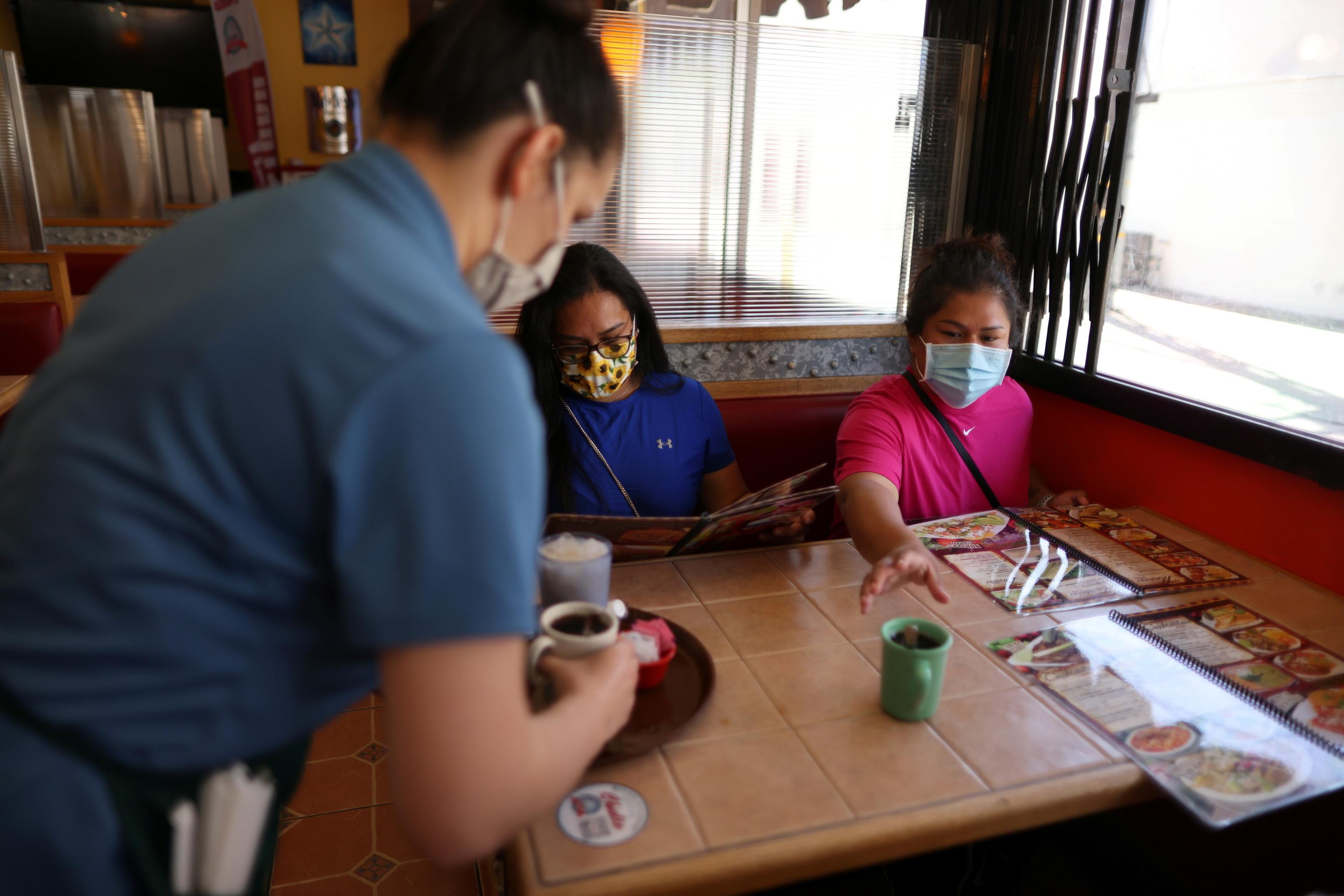 Unas mujeres llevan mascarilla en un restaurante mexicano en Los Ángeles (EEUU).