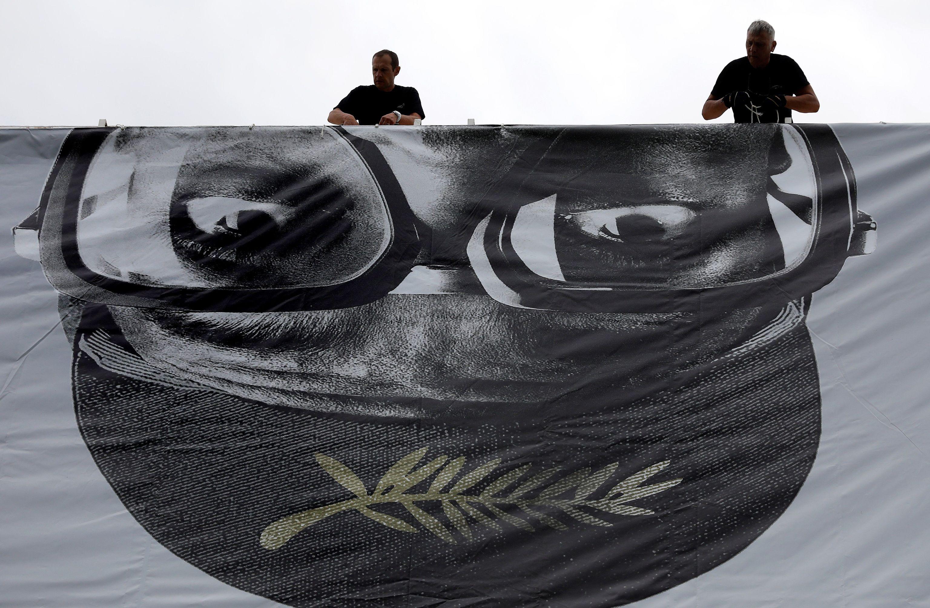 UNos operarios colocan el cartel del festival que protagoniza Spike Lee.