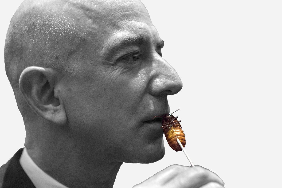 Jeff Bezos comiendo una cucaracha durante la cena del club de los exploradores en el Waldorf Astoria de Nueva York.