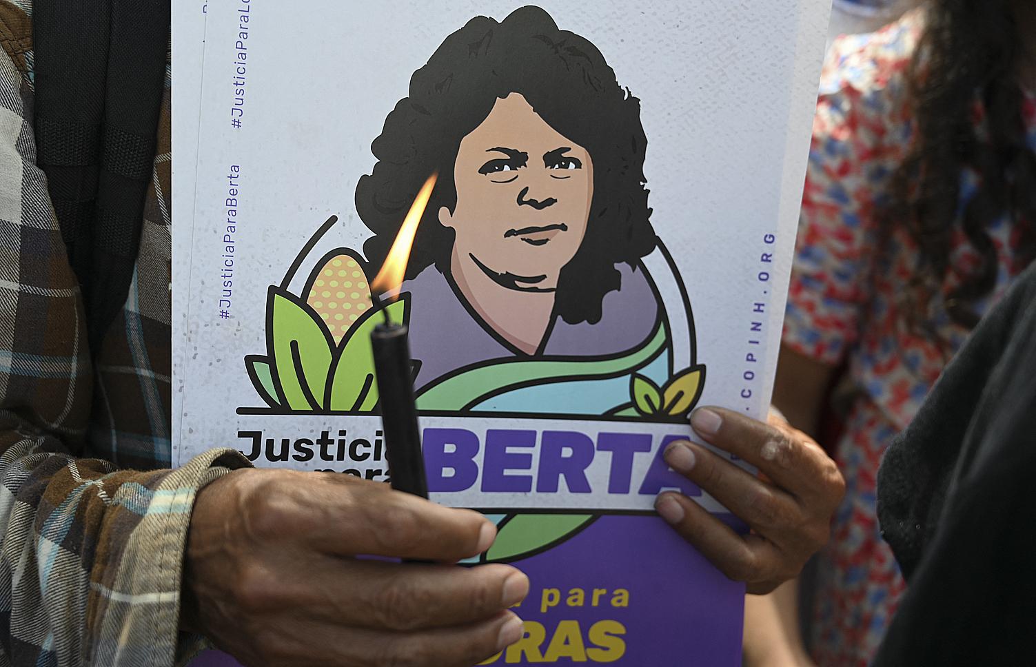 Un activista espera la sentencia mientras muestra una vela y una ilustración de la ambientalista.