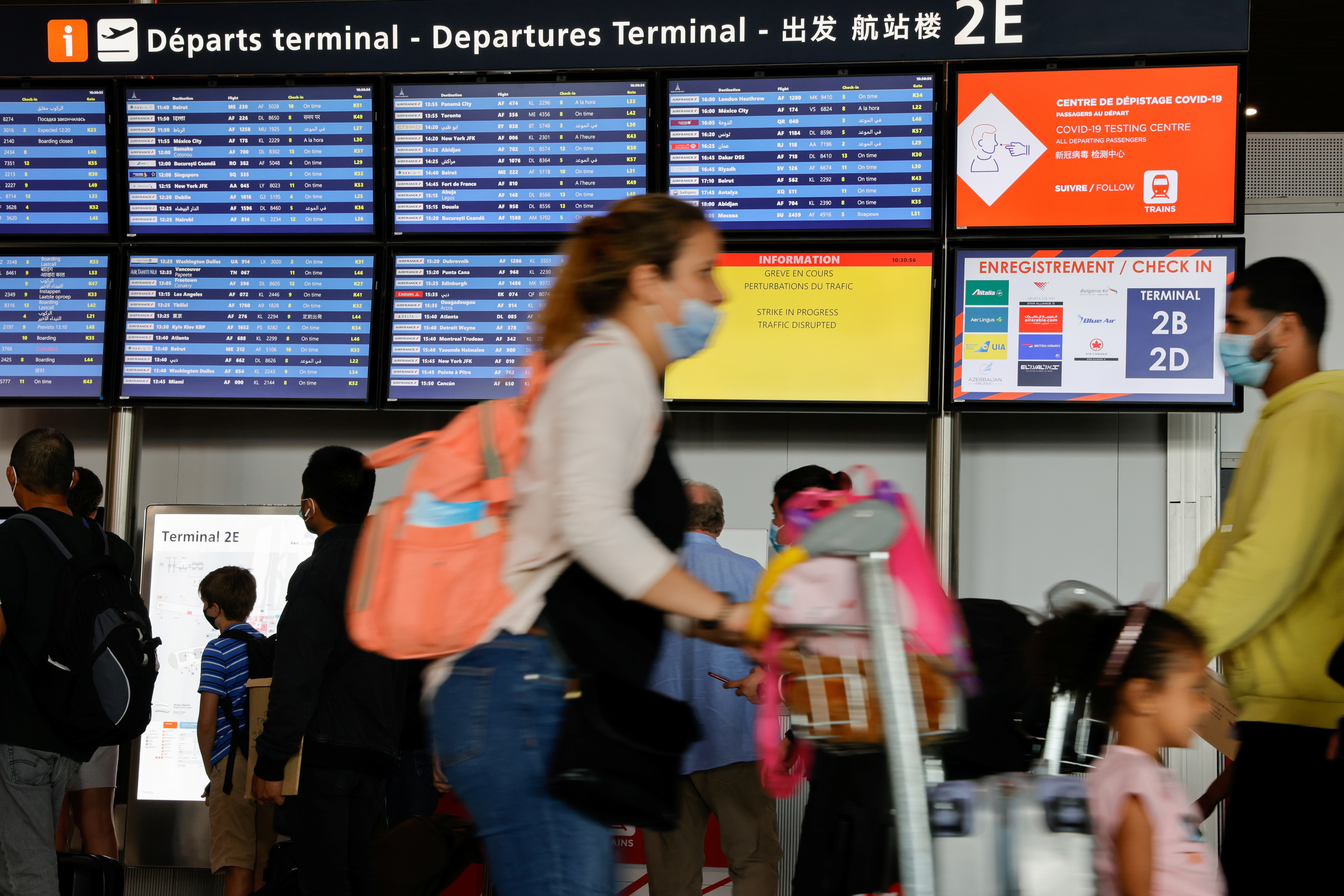Los pasajeros esperan frente a las pantallas que anuncian los vuelos y la huelga de los trabajadores de Groupe ADP (Aeroports de Paris), en el aeropuerto Charles-de-Gaulle en Roissy, cerca de París