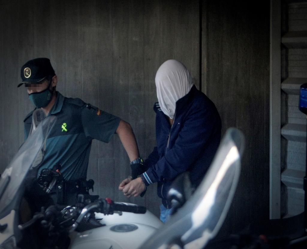 Un guardia civil traslada a uno de los presuntos asesinos de Samuel Luiz, con el rostro oculto.
