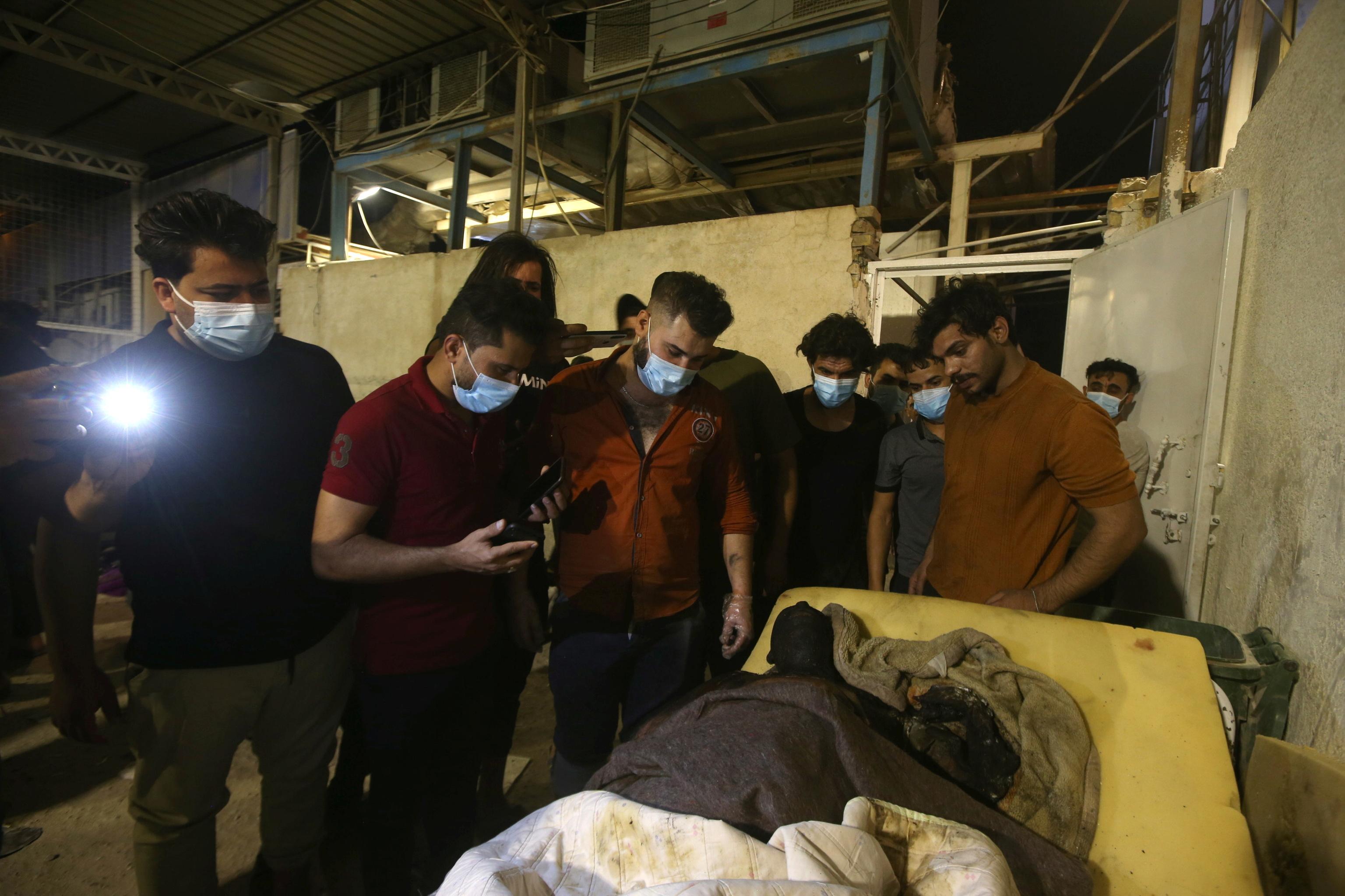 Vecinos protegidos con mascarilla inspeccionan el cadáver de una de las personas fallecidas en el incendio.