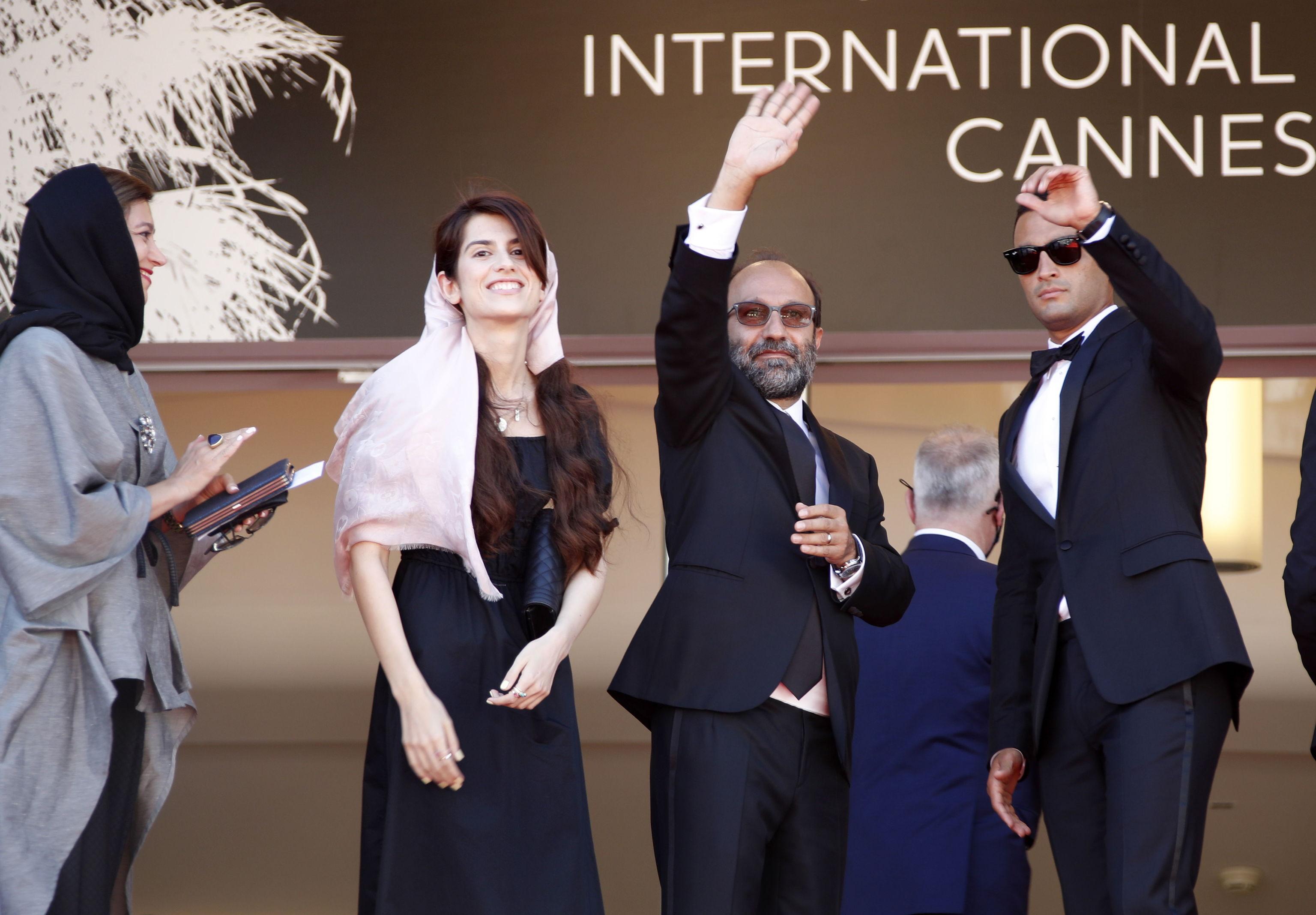 El director iraní Asghar Farhadi llega rodeado de su equipo a la presentación de 'A hero'.