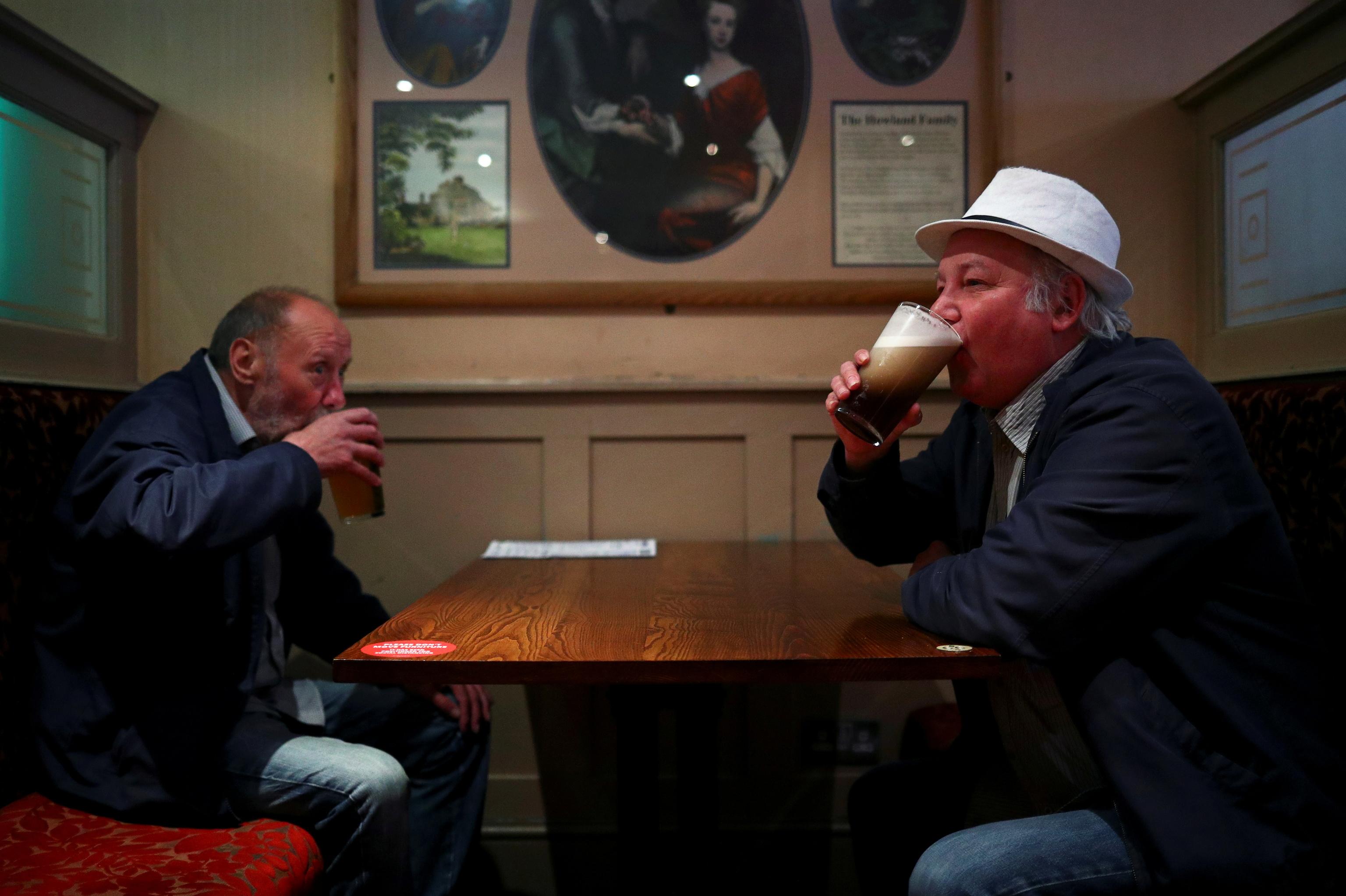 Dos hombres beben cerveza en un pub de Londres.
