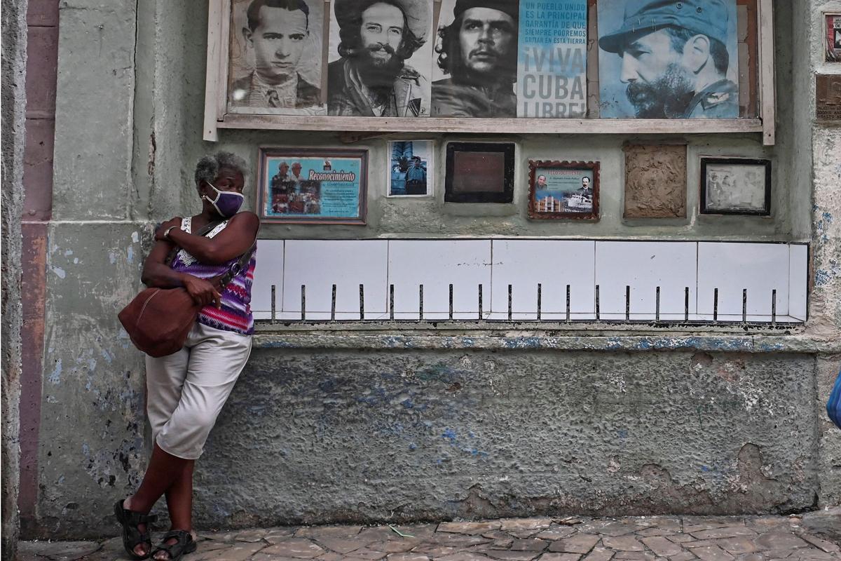 Una mujer junto a fotos de difuntos líderes cubanos.
