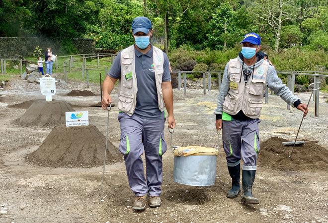 Dos empleados sacan el cocido de las profundidades volcánicas.