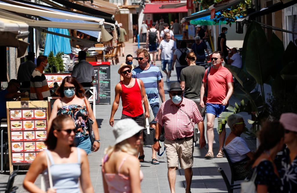 Paseantes con y sin mascarilla en Sitges (Barcelona)