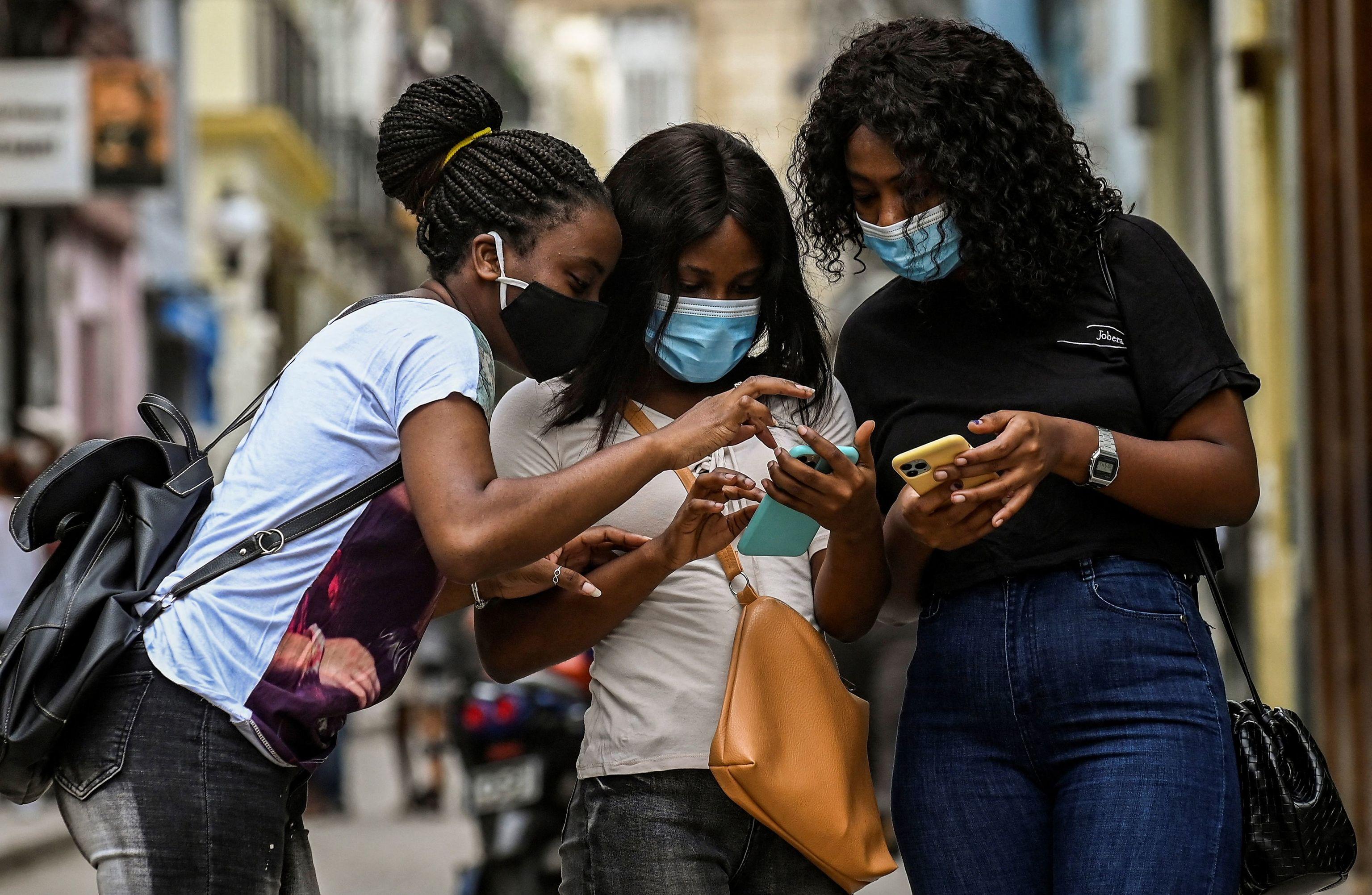 Varias mujeres utilizan su teléfono móvil, en La Habana.