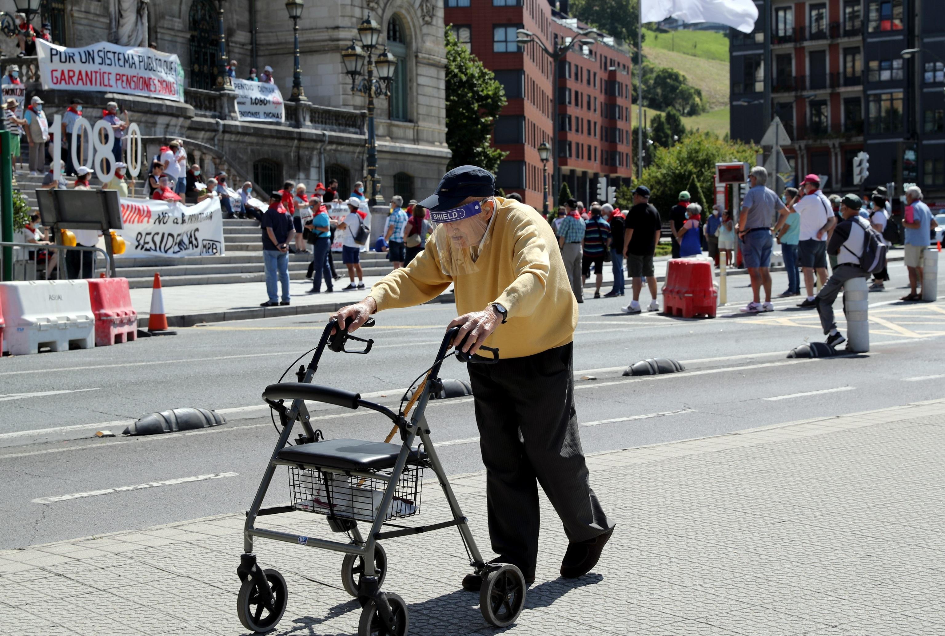 Un hombre camina junto a una marcha de pensionistas en Bilbao. EFE