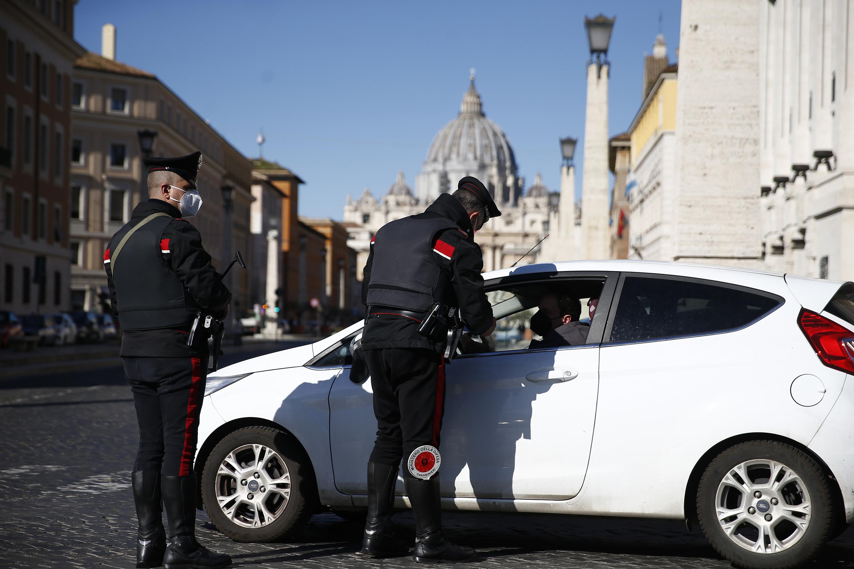 Agentes de la policía de los Carabinieri detienen un coche en un control de carretera cerca de la Basílica de San Pedro, en el fondo, en Roma