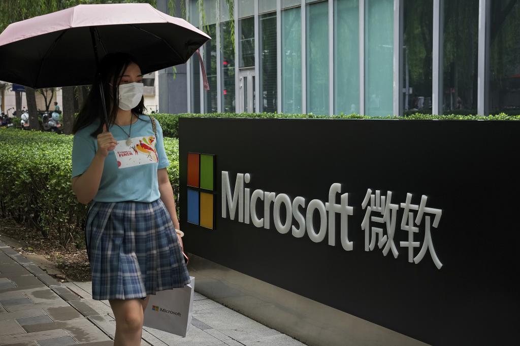 Una mujer pasea delante de la sede de Microsoft en Pekín.
