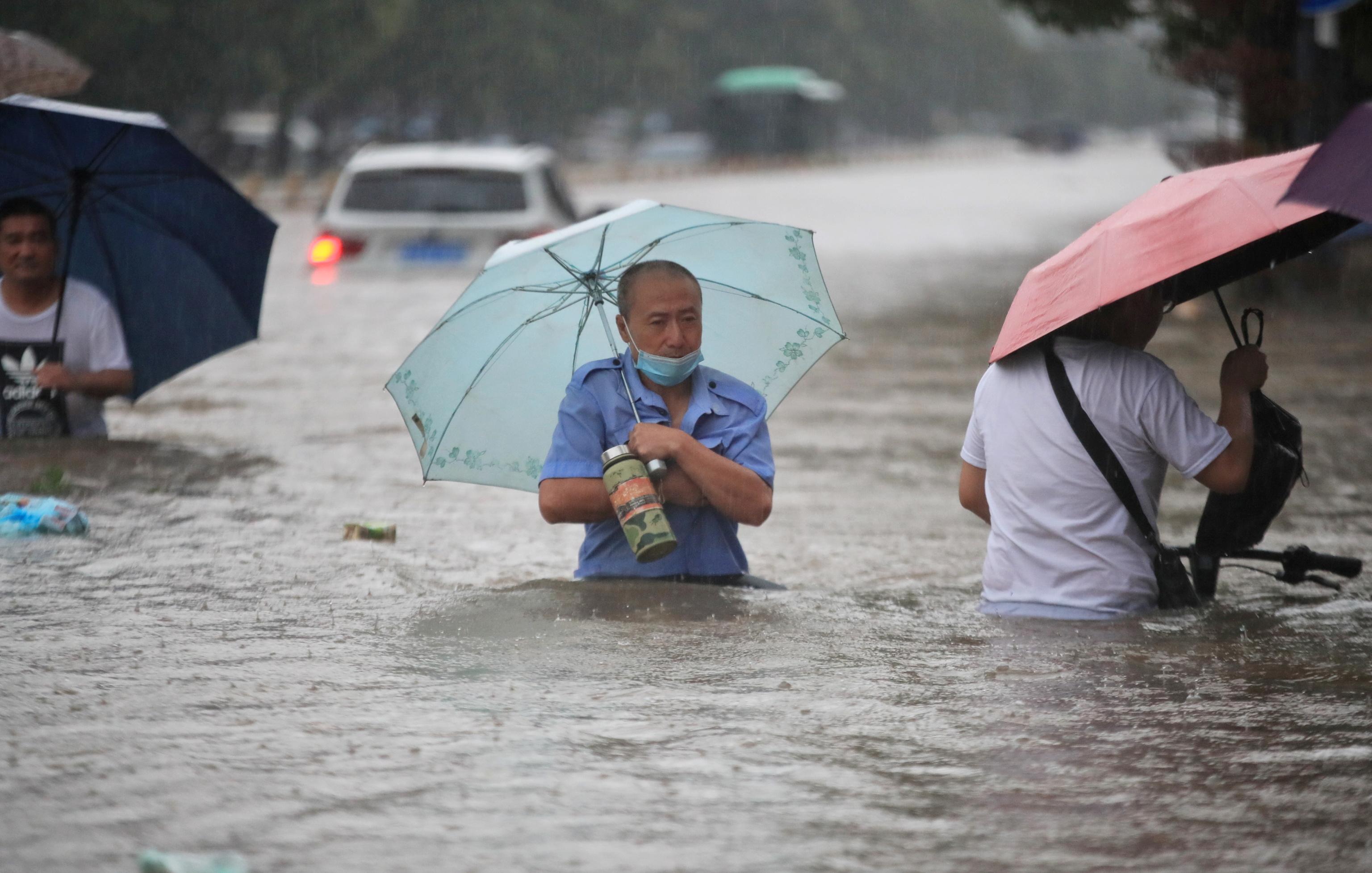 Residentes avanzan por avenidas inundadas en Zhengzhou, China.
