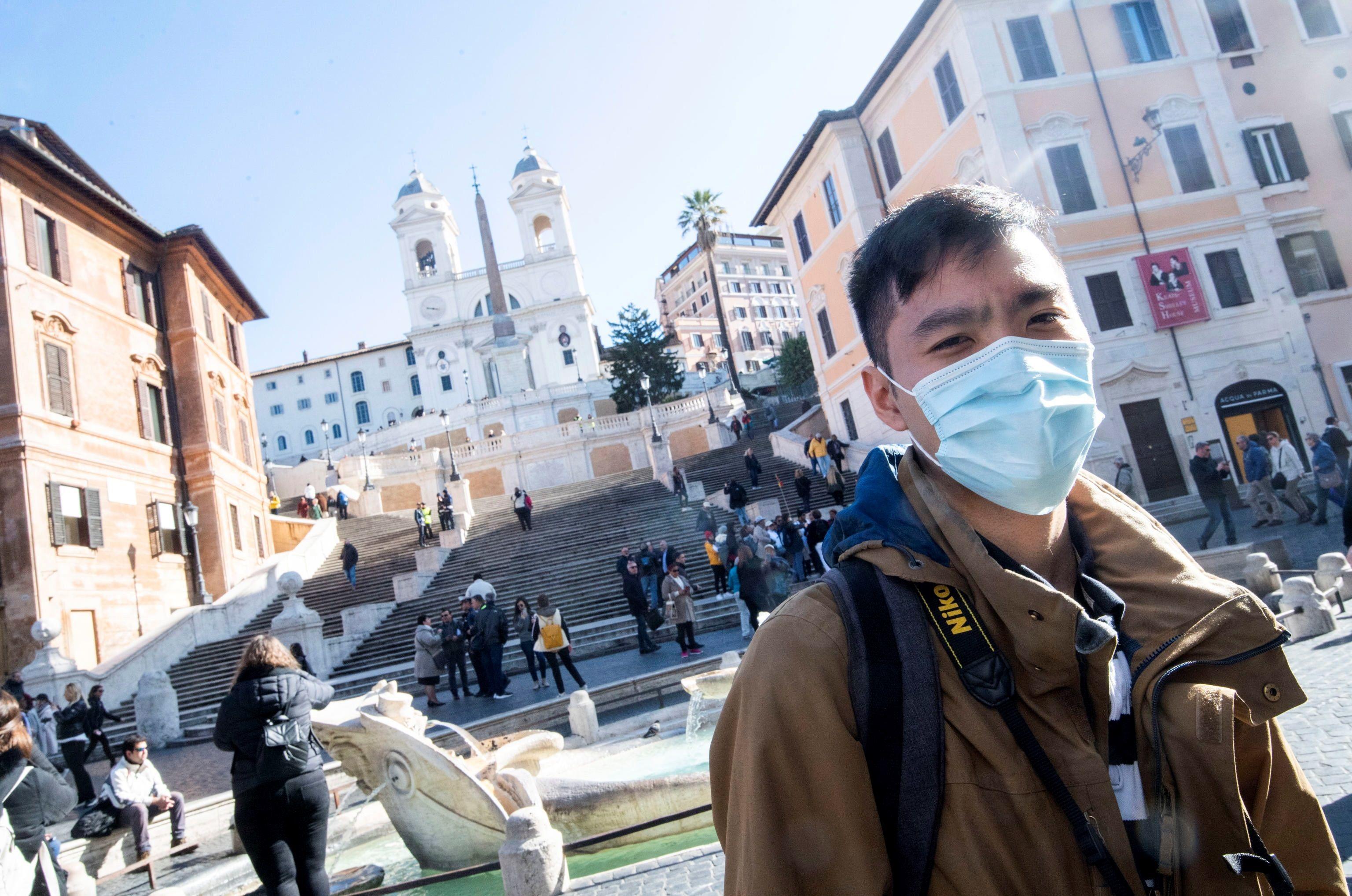 Un turista pasea con mascarilla por la plaza de España, en Roma.