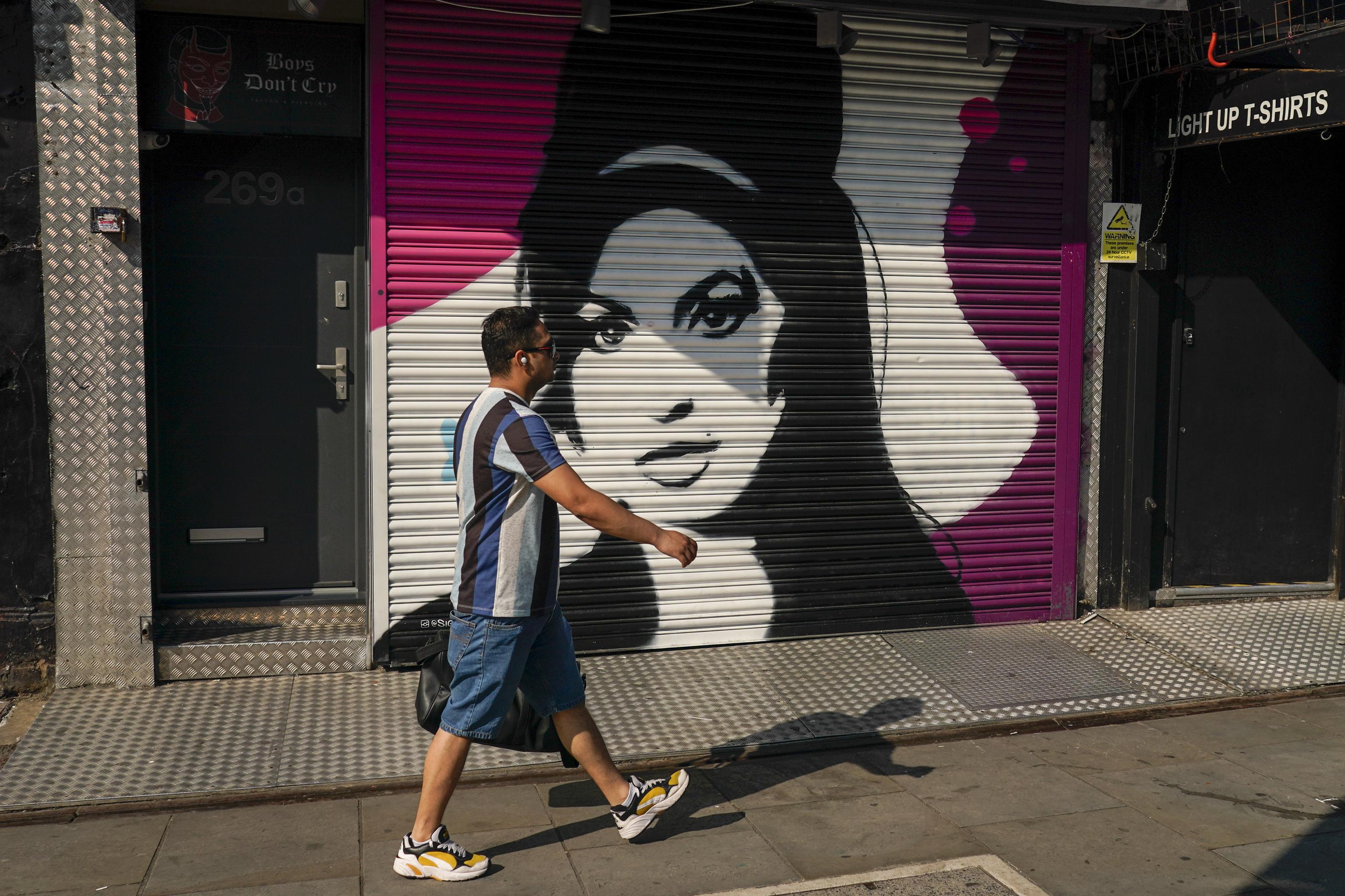 Un hombre camina frente a un mural de Amy Winehouse en Camden, Londres.