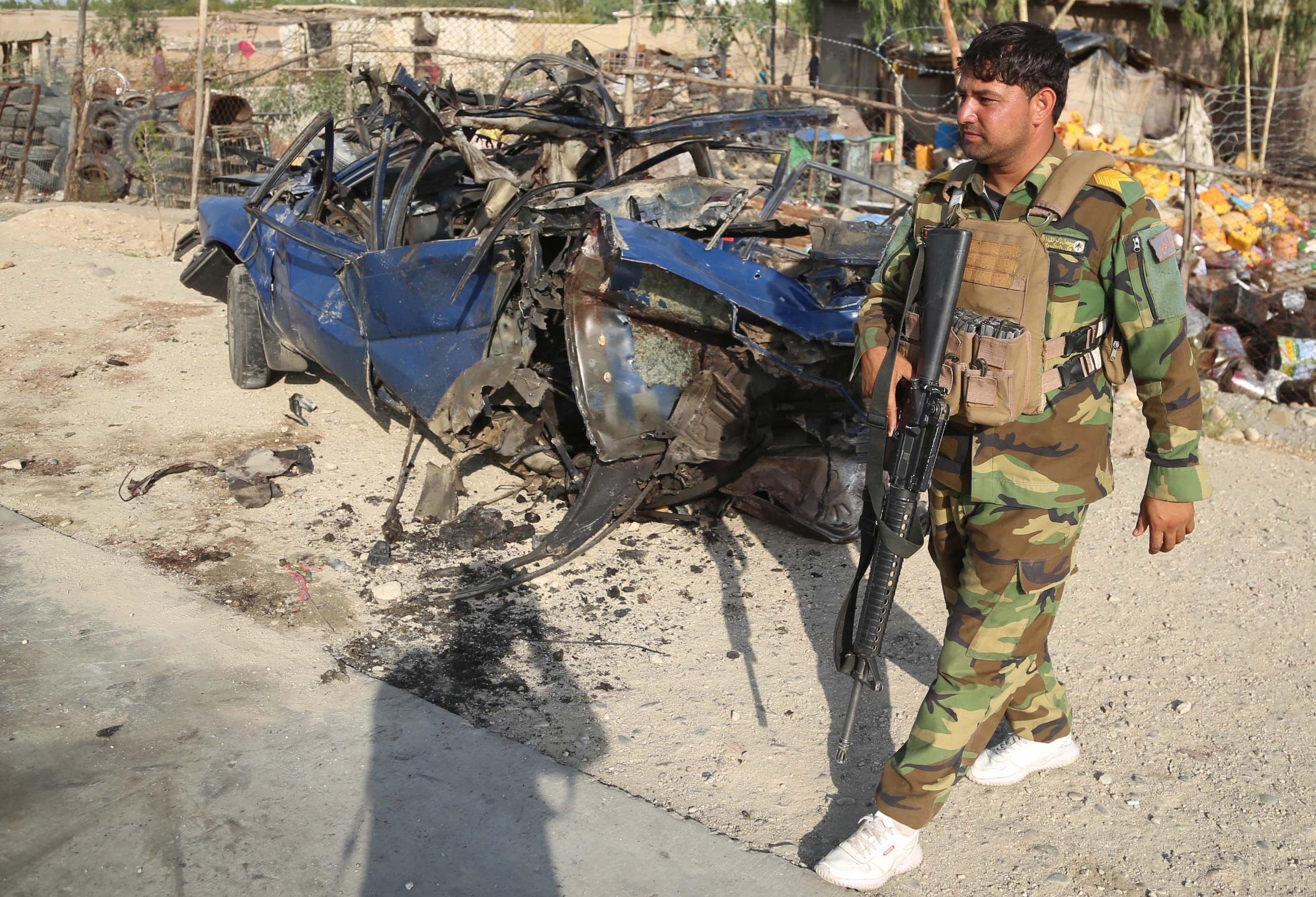 Oficiales de seguridad afganos inspeccionan el lugar de la explosión de una bomba, en Jalalabad.