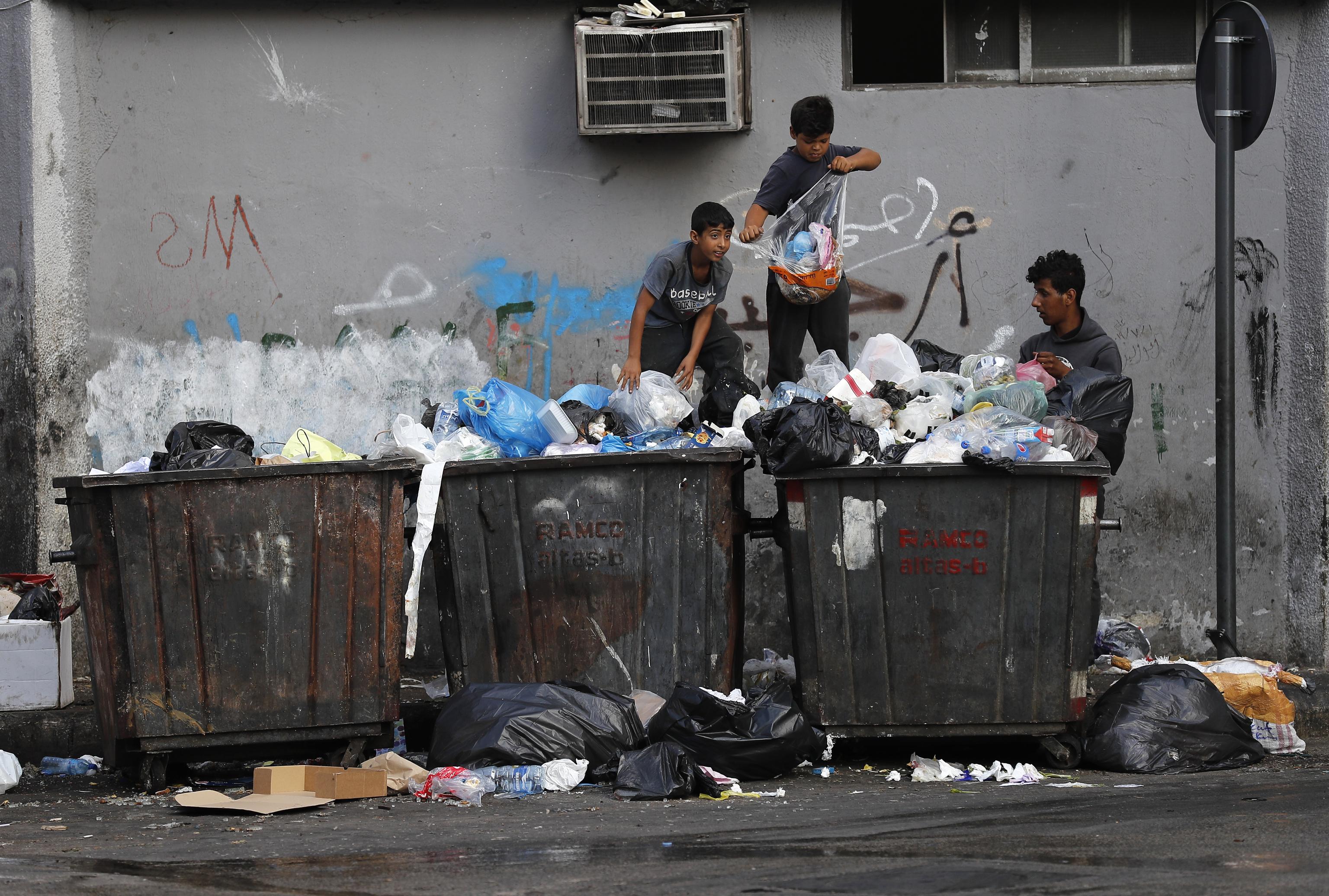 Niños escarban entre la basura en Beirut.