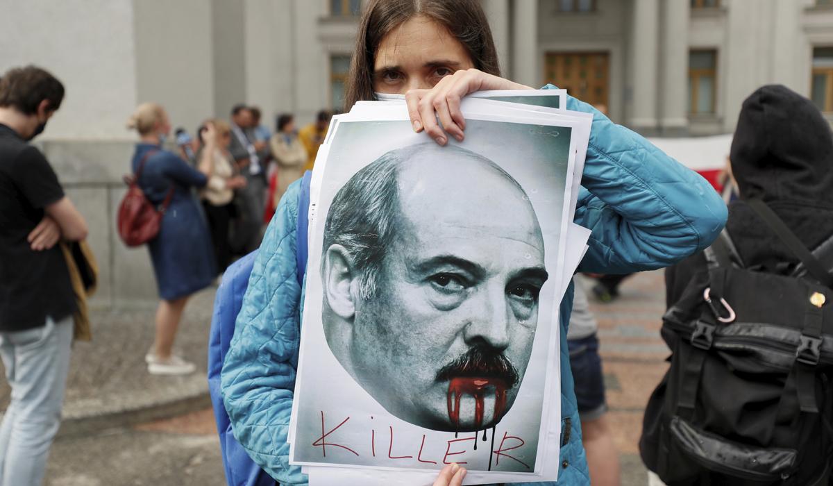 """Una activista enseña en Kiev una pancarta con el rostro de Lukashenko y la palabra """"asesino""""."""
