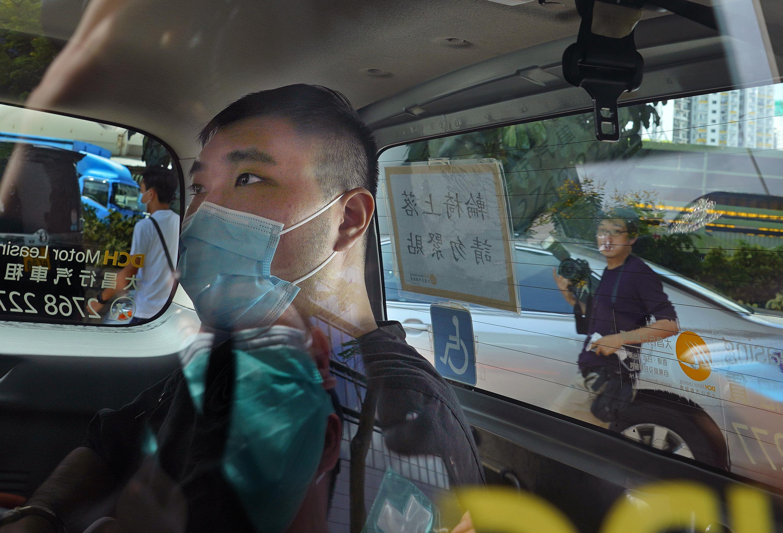 """En esta foto de archivo del 6 de julio de 2020, Tong Ying-kit llega a un tribunal en un furgón policial en Hong Kong. El Tribunal Superior de Hong Kong emitirá el veredicto el martes 27 de julio de 2021 para la primera persona acusada en virtud de la Ley de Seguridad Nacional de Hong Kong. Tong fue detenido en julio de 2020 después de conducir su moto contra un grupo de policías mientras llevaba una bandera con el lema de protesta """"Liberar Hong Kong"""". Fue acusado de incitar al separatismo y al terrorismo.   Traducción realizada con la versión gratuita del traductor www.DeepL.com/Translator"""