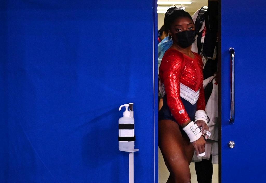 Simone Biles con mascarilla sale de un puesto médico durante la final por equipos.