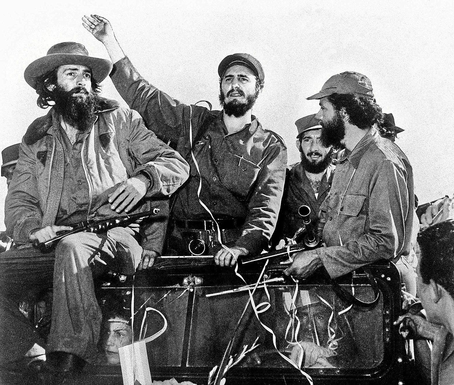 """Foto de archivo de la Revolución Cubana. El rebelde cubano (c) rodeado de miembros de su guerrilla """"Movimiento 26 de Julio"""", saludan desde un jeep el 8 de enero de 1959, a su entrada en La Habana tras su victoria sobre las fuerzas del general Fulgencio Batista."""